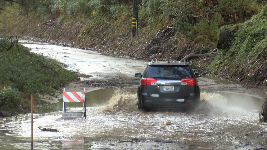 CAR DRIVES THROUGH FLOODED STREET