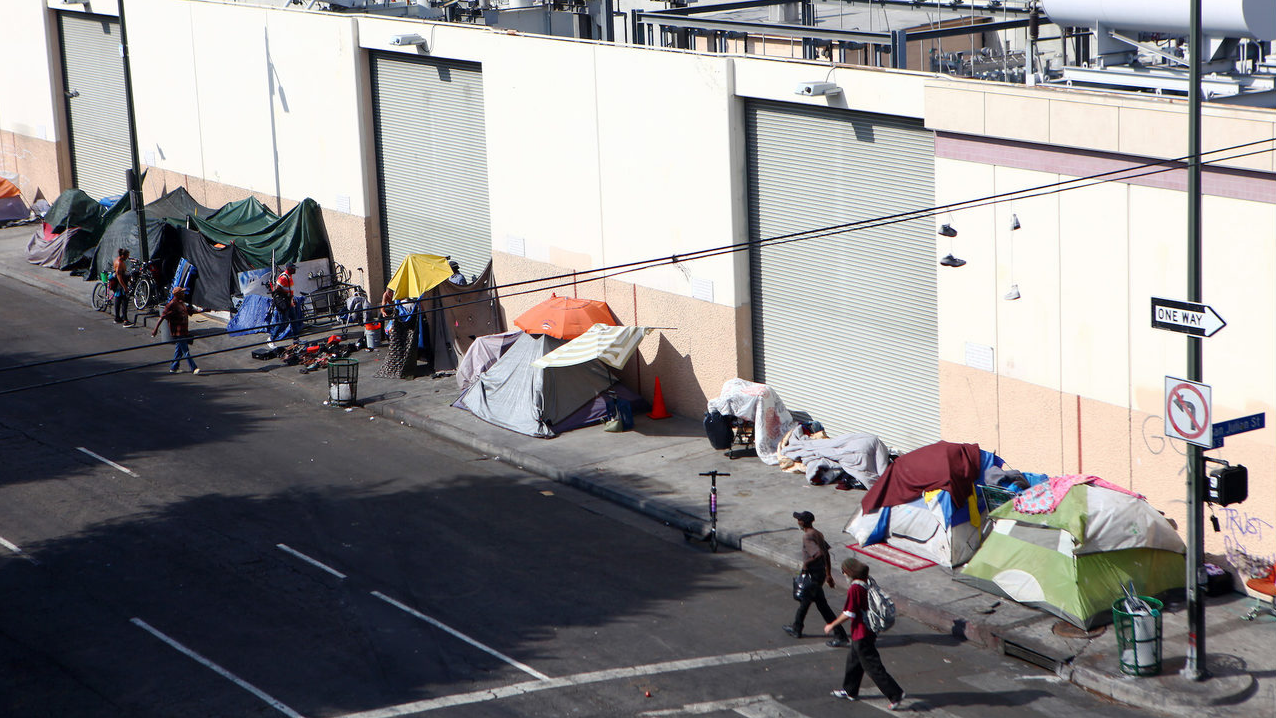 People walk past a homeless tent encampment in Skid Row on Sept. 16, 2019, in Los Angeles.