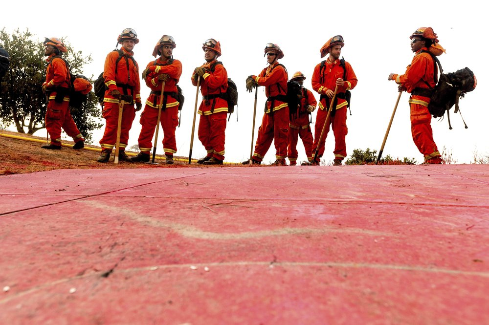 In this Aug. 17, 2020, file photo, inmate firefighters - notable by their bright orange fire gear compared to the yellow worn by professional firefighters - prepare to take on the River Fire in Salinas, Calif. California could change its constitutional ban on slavery to remove the words