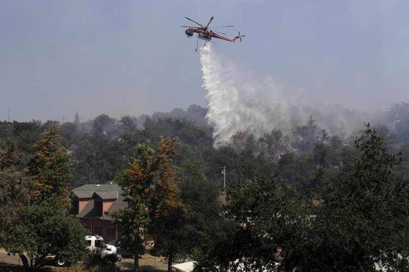 In this June 11, 2020, file photo, a helicopter drops water near a structure as crews fight the Skyline Fire in San Diego County near Jamul, Calif. California's attorney general is challenging some of the state's largest suburban development projects as local officials weigh the risk of increasingly devastating wildfires against the most populous state's dire need for more housing. Attorney General Xavier Becerra on Wednesday, March 17, 2021, backed lawsuits opposing San Diego County's approval of environmental reviews for two projects in a very high wildfire hazard zone southeast of San Diego.