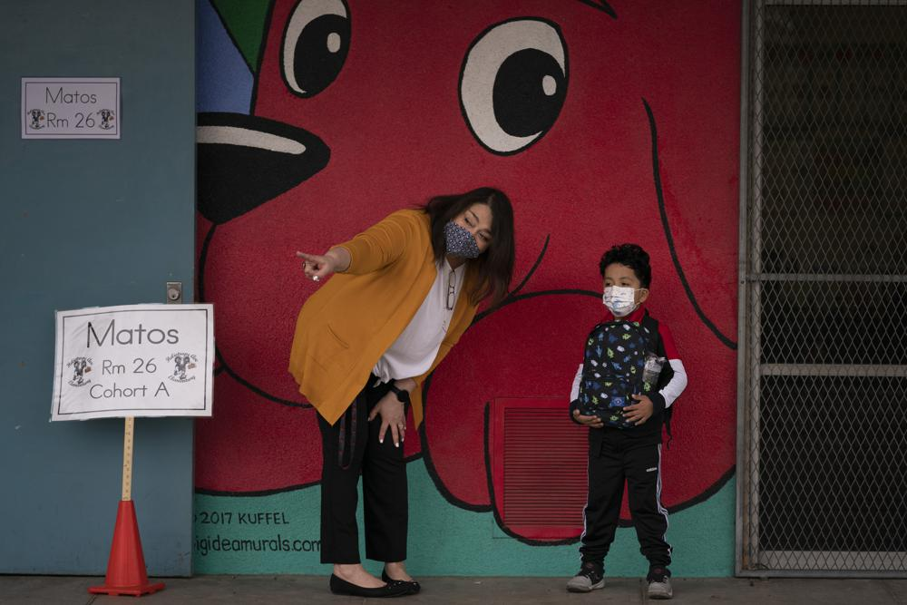 FILE - In this April 13, 2021, file photo, kindergarten teacher Lilia Matos and her student Jesus Mendez stand outside their classroom on the first day of in-person learning at Heliotrope Avenue Elementary School in Maywood, Calif. California's public schools have seen a