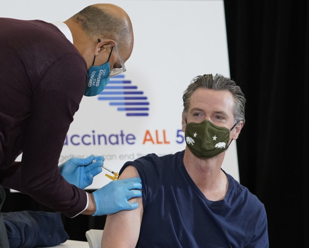 Dr. Mark Ghaly, Secretary, California Health and Human Services, left, inoculates California Gov. Gavin Newsom, right, at the Baldwin Hills Crenshaw Plaza in Los Angeles Thursday, April 1, 2021. Newsom was vaccinated with the new one-dose Janssen COVID-19 vaccine by Johnson & Johnson.