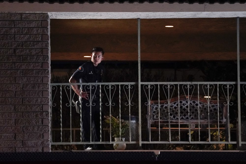 A police officer surveys the scene after a shooting at an office building in Orange, Calif., Wednesday, March 31, 2021. The shooting killed several people, including a child, and injured another person before police shot and wounded the suspect, police said.