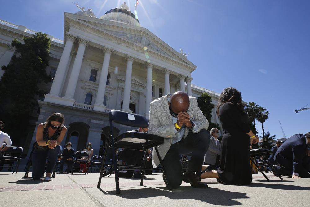 FILE - In this June 9, 2020, file photo, Assemblyman Mike Gipson, D-Carson, bows his head as he and other members of the California Legislature kneel to honor George Floyd at the Capitol in Sacramento, Calif. California lawmakers on Wednesday, May 26, 2021, advanced three criminal justice reform bills including one that could end the careers of police officers found to have committed various wrongs, after a similar measure died without a final vote last year despite national outrage over the death of George Floyd in the custody of Minneapolis police.