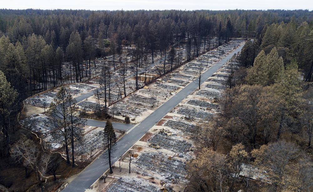 FILE - In this Dec. 3, 2018, file photo, charred footprints of homes leveled by the Camp Fire line the streets at the Ridgewood Mobile Home Park retirement community in Paradise, Calif. A trust approved by a federal judge to help compensate victims of deadly California wildires sparked by Pacific Gas & Electric equipment paid survivors just $7 million while racking up $51 million in overhead in its first year of operation, KQED News reported.
