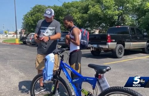 Michael Lynn (left) stands next to Donte Franklin and his new bicycle. The biker charity group My Riding Buddies Oklahoma and Bikers for Elves gave Franklin the bike after they saw Lynn's facebook post about Franklin's daily 17-mile walk to work.