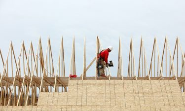 A contractor works on the roof of a house under construction at the Lennar Corp. Tree Tops community development in Lancaster