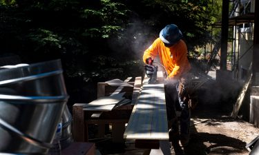 A contractor uses a saw to cut siding for a house under construction in Walnut Creek