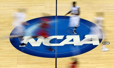 Mississippi Rebels and Xavier Musketeers players run by the NCAA logo at mid-court.