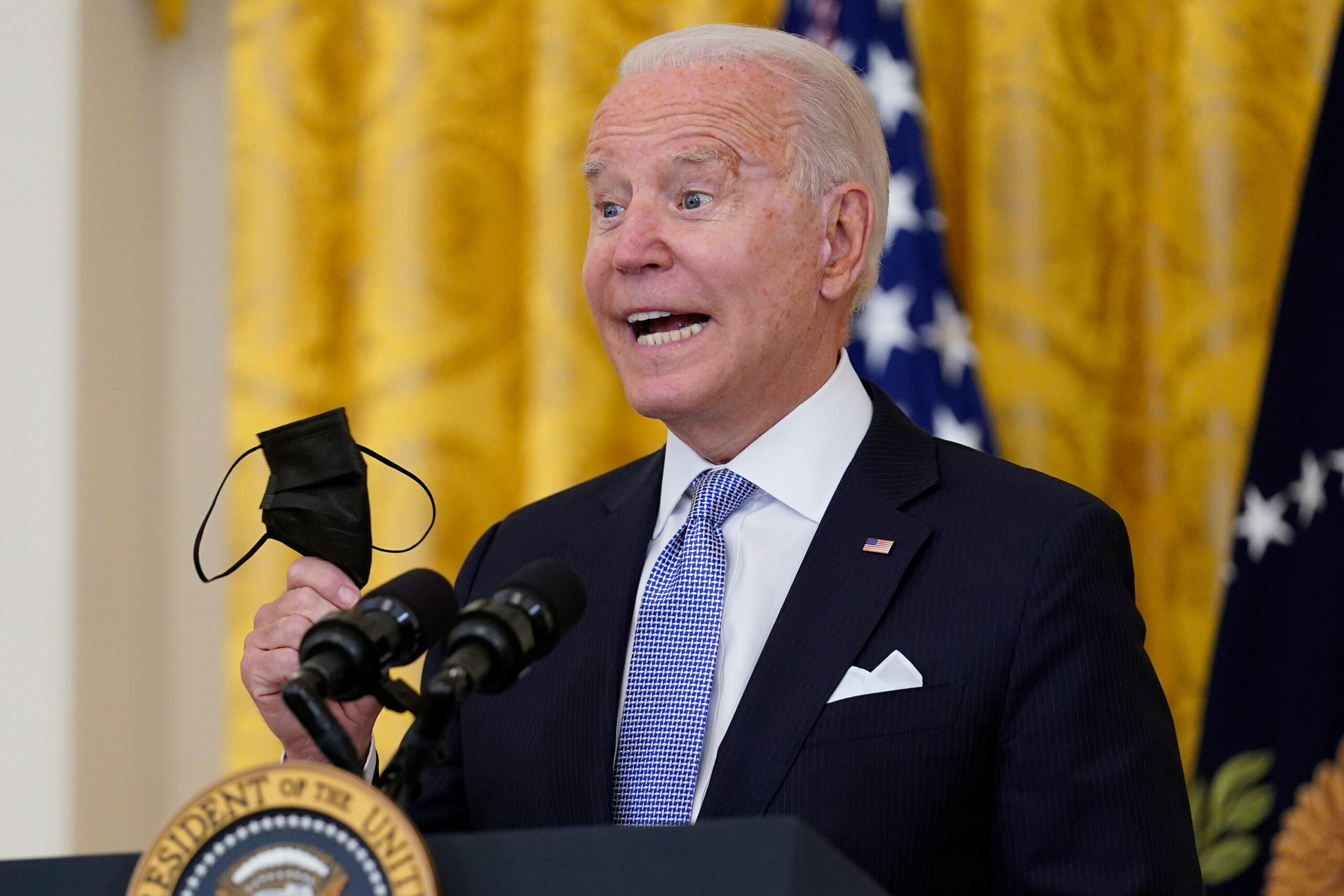 <i>Susan Walsh/AP</i><br/>President Joe Biden holds his face mask as he speaks in the East Room of the White House in Washington