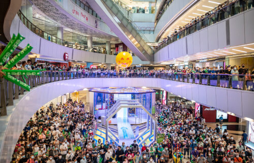 People are shown at a shopping mall in Hong Kong watching Siobhan Haughey swim in the 100-meter freestyle Olympics final on Friday. Hong Kong police have arrested a man after he allegedly booed the Chinese national anthem while watching an Olympics award ceremony inside a shopping mall..
