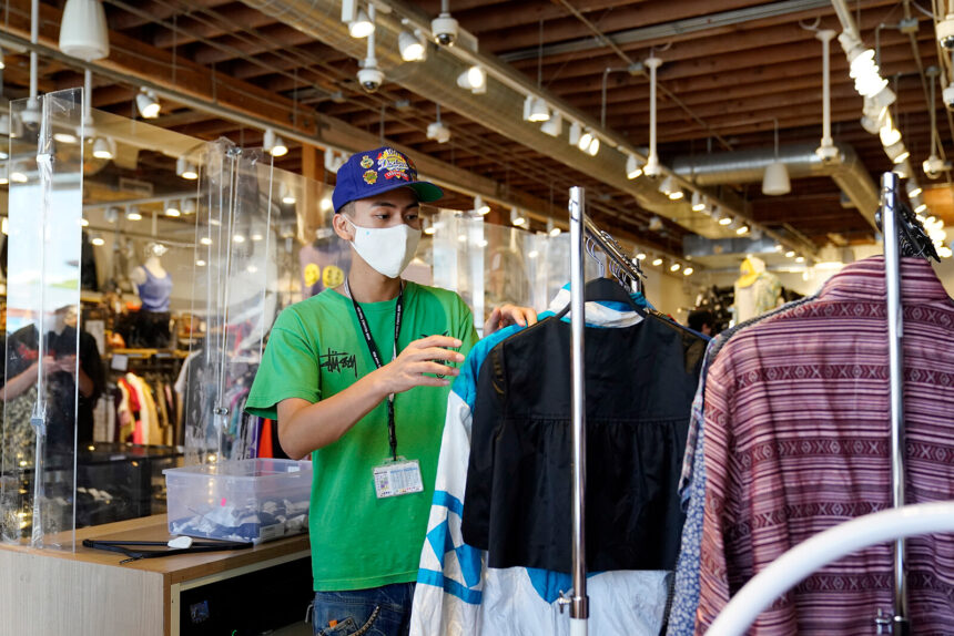 An employee sorts a clothing rack at 2nd Street second hand store July 19 in the Fairfax district of Los Angeles.