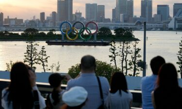 Visitors look at the Olympic rings floating in the water at Odaiba Marine Park