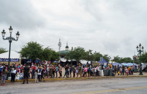 Migrants who were sent back to Mexico under Title 42 wait in line for food and supplies in a camp across the US-Mexico border in Reynosa