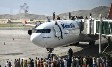 Afghan people climb atop a plane as they wait at the Kabul airport on Monday