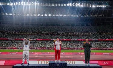 Raven Saunders performing her X gesture on the shot put medal podium.