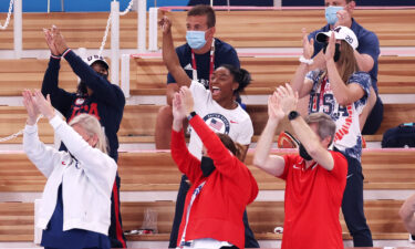 Simone Biles cheers with teammates Jordan Chiles (left) and Grace McCallum (right) from the stands during the women's vault final.