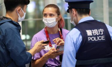 Belarusian athlete Kristina Timanovskaya talks with police at Haneda international airport in Tokyo on August 1.