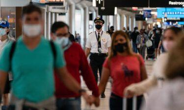 People wearing protective masks walk through Hartsfield-Jackson Atlanta International Airport.