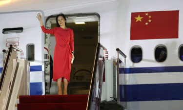 Huawei executive Meng Wanzhou waves as she steps out of an airplane after arriving at Shenzhen Bao'an International Airport in Shenzhen