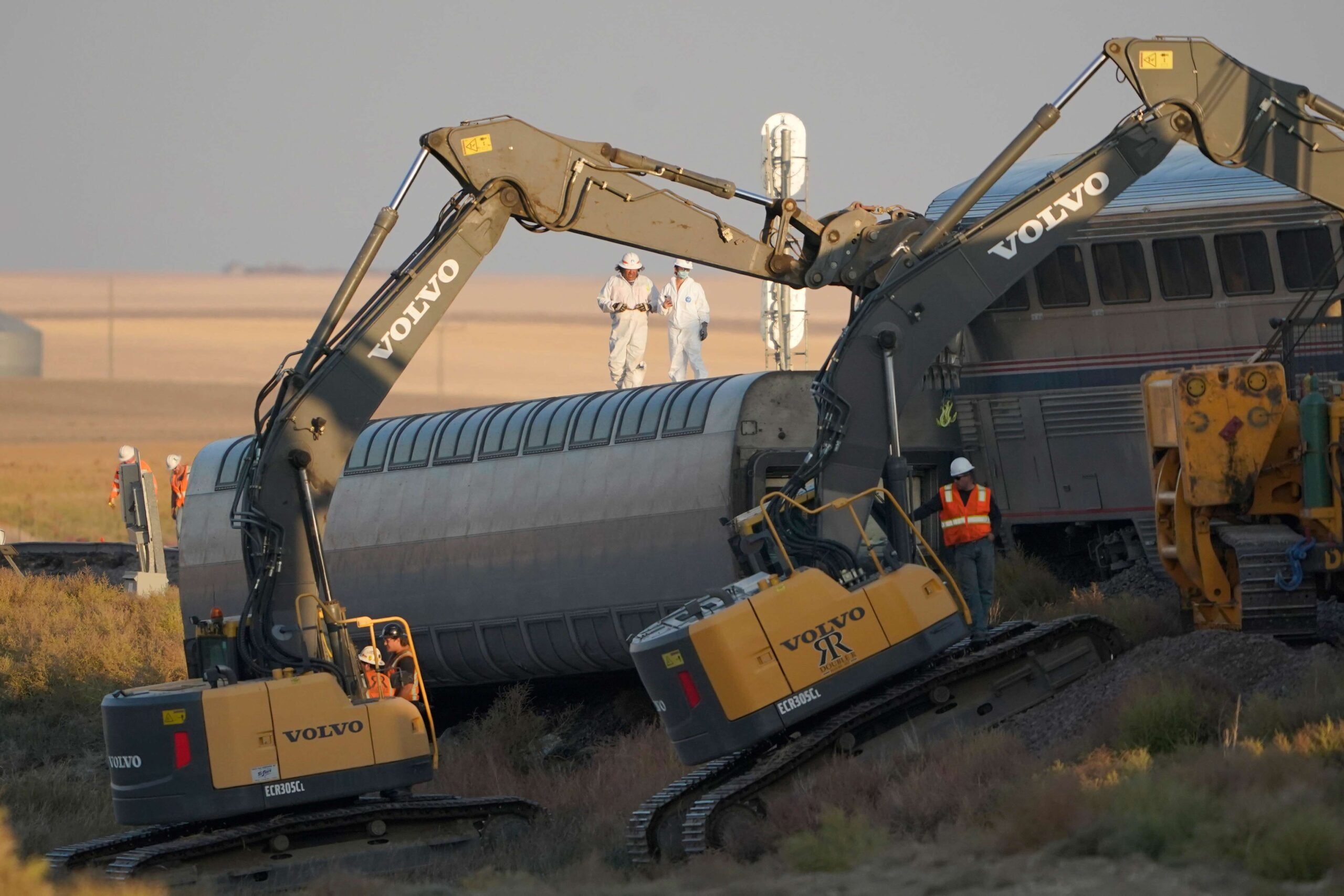 <i>Ted S. Warren/AP</i><br/>Workers stand on a train car on its side as front-loaders prop up another train car