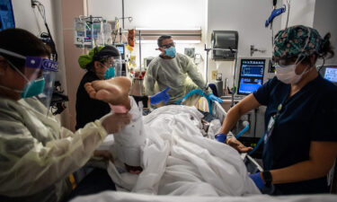Health care workers attend to a patient with Covid-19 at the Cardiovascular Intensive Care Unit at Providence Cedars-Sinai Tarzana Medical Center in Tarzana