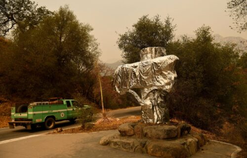 A US Forest Service vehicle drives past the Sequoia National Park historic park entrance sign wrapped in fire resistant foil along Generals Highway during a media tour of the KNP Complex fire in the Sequoia National Park near Three Rivers