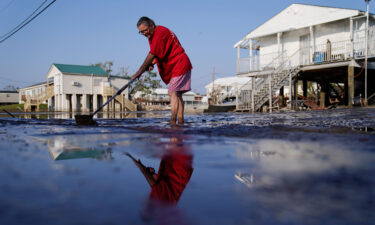 Cindy Rojas cleans mud and floodwater from her driveway in Lafitte