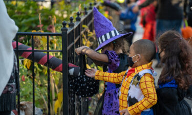 Children receive treats by candy chutes while trick-or-treating for Halloween in Woodlawn Heights on October 31