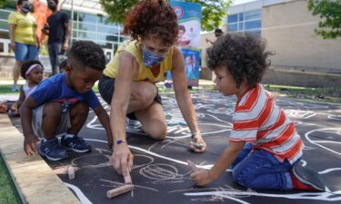 Children from a childcare center complete a mural celebrating the launch of the Child Tax Credit on July 14